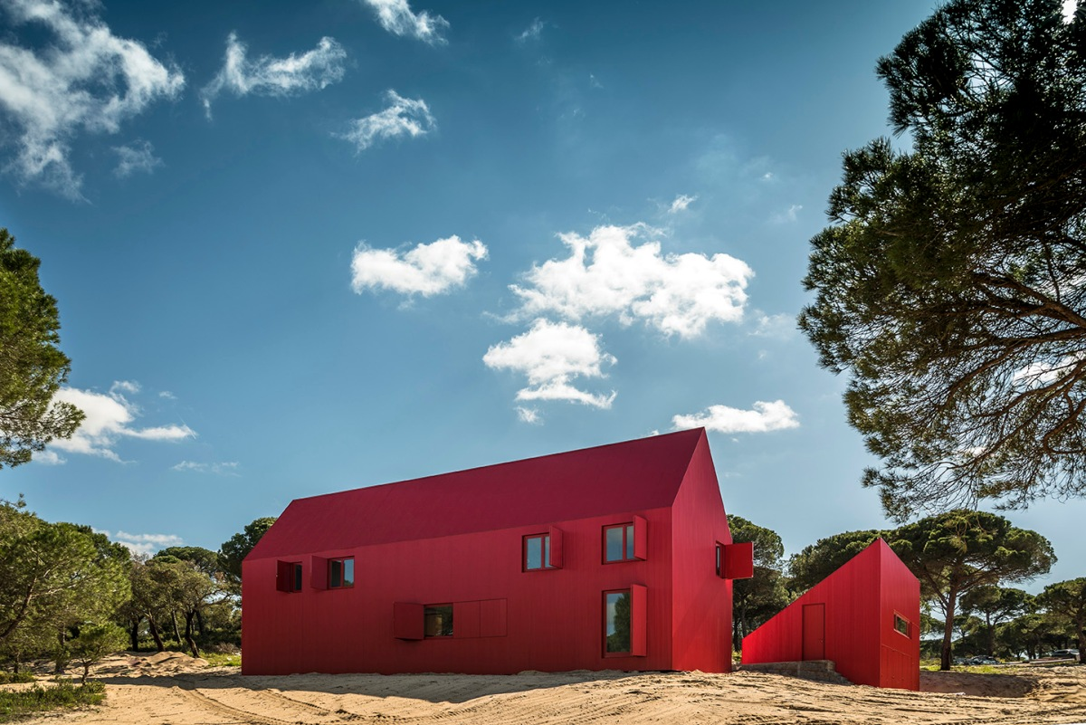 Luís Rebelo de Andrad disrupts portuguese oak forest with vibrant red barn